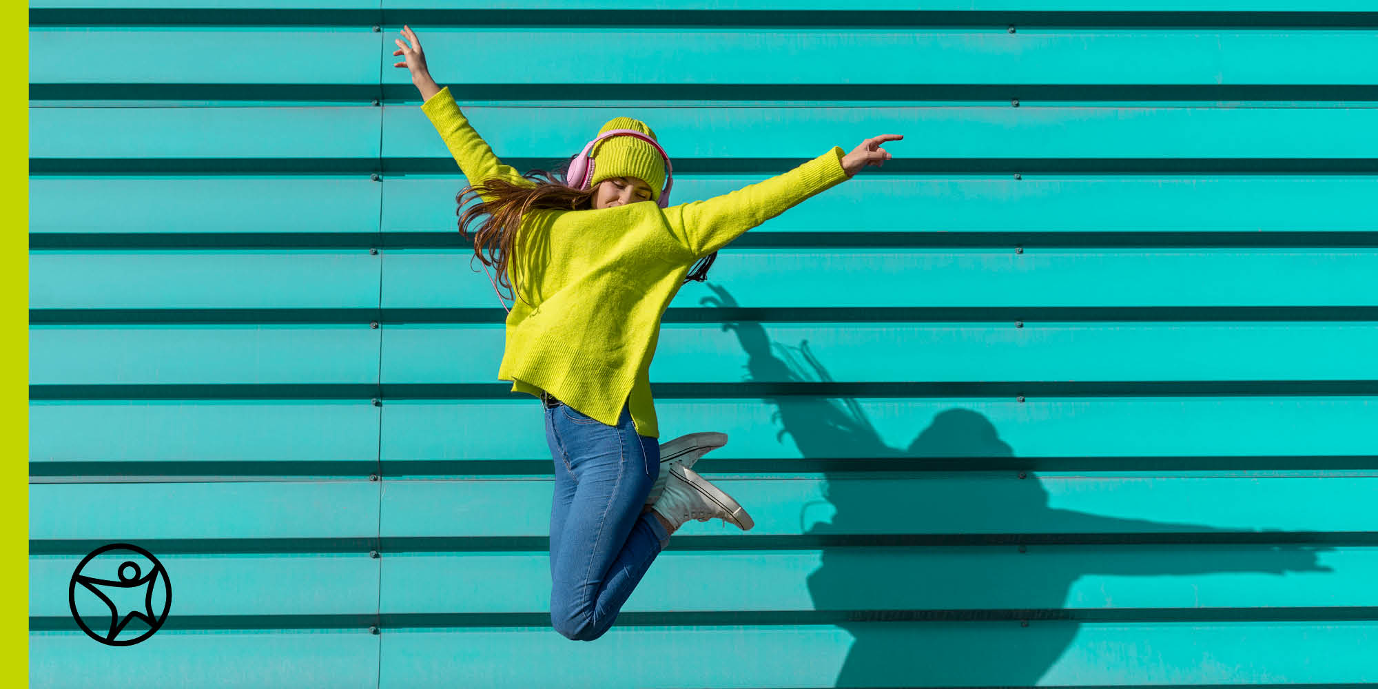 High school student jumping in front of a wall