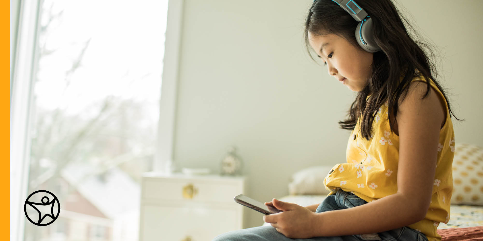 Young girl playing a game on a mobile phone wearing headphones