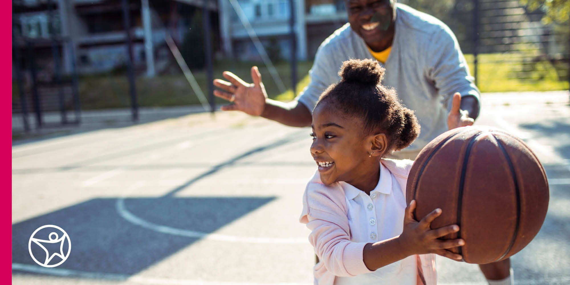 Elementary school-aged girl playing basketball with an adult male